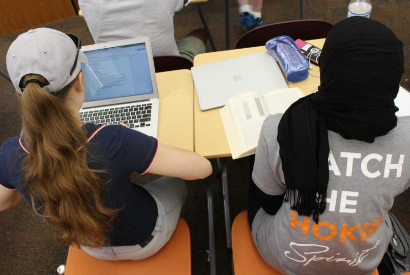Two girls sit at their desks during class, one wears a baseball cap and the other a hijab.