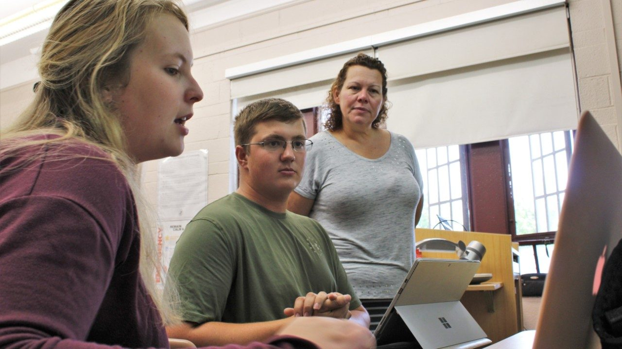Kim Morgan stands, advising two students as they look at data on their laptop.