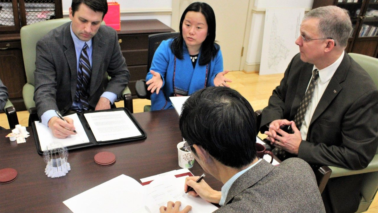 Nankai University signs 3-plus-2 agreement with Nankai University in Dean Grant's office with Associate Professor Wen You and Assistant Director of Global Programs Ben Grove.