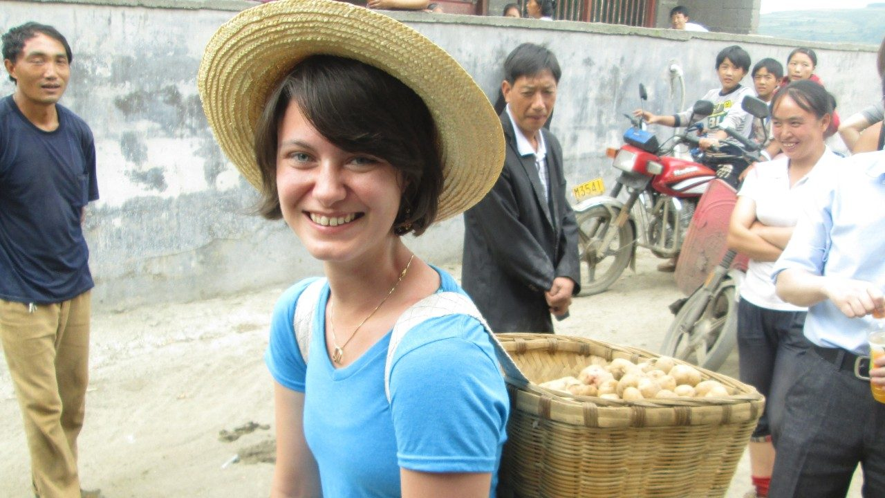 Stephanie Myrick carries traditional potato basket from field to market in China.