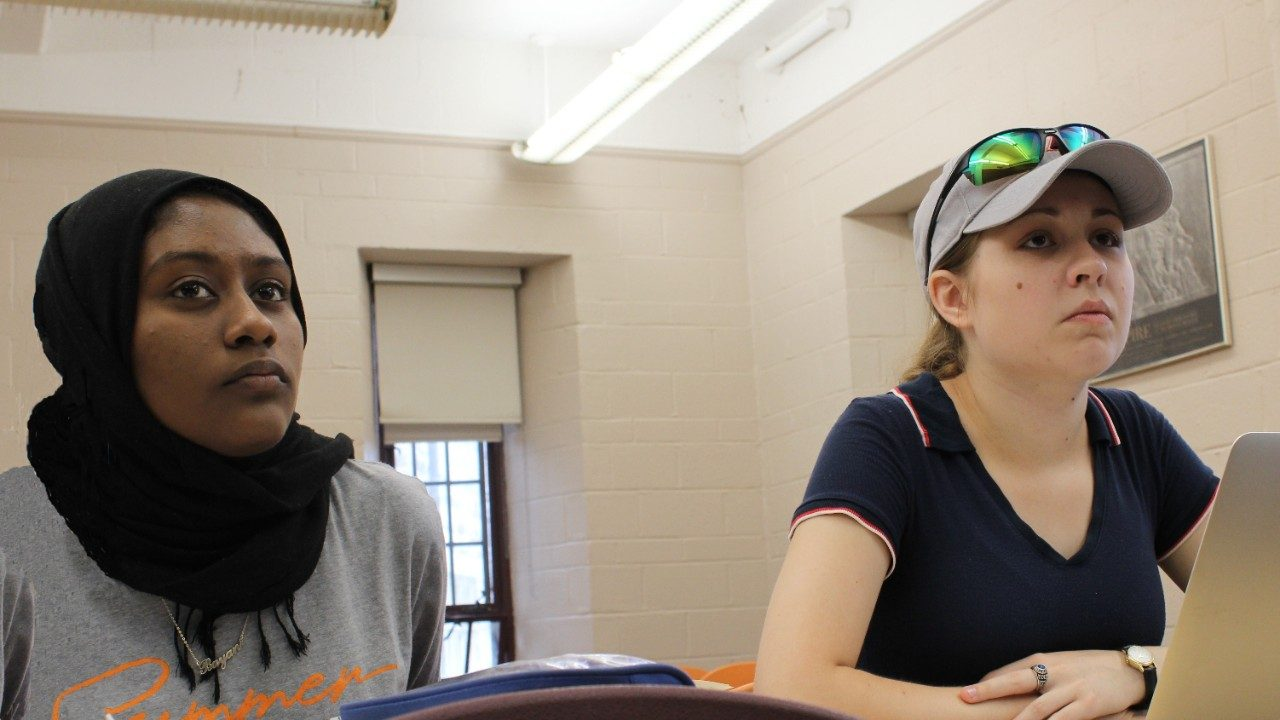 Two girls look up from their desks during class, one wears a baseball cap and the other a hijab.