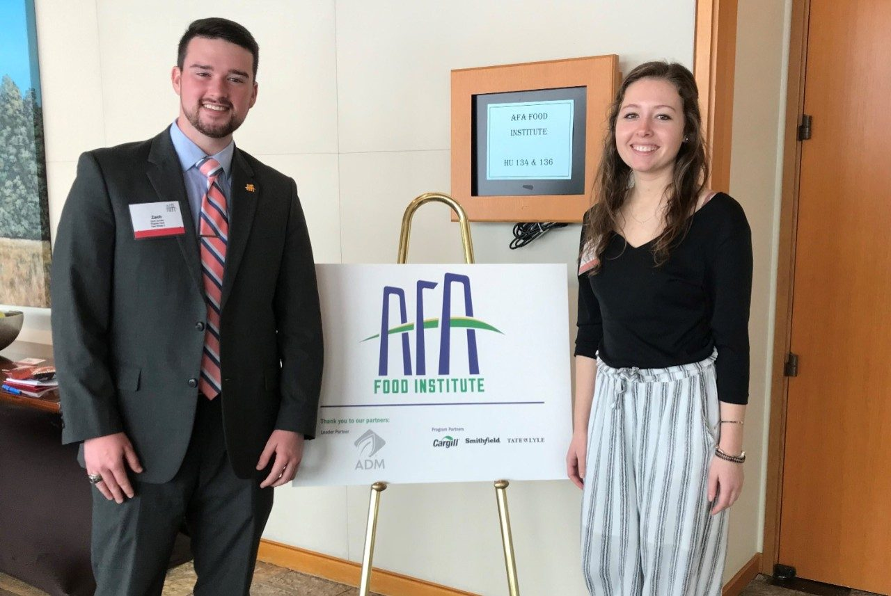 Zach Jacobs and Margaret Benson stand next to an AFA sign at the 2019 Agriculture Future of America Food Institute.