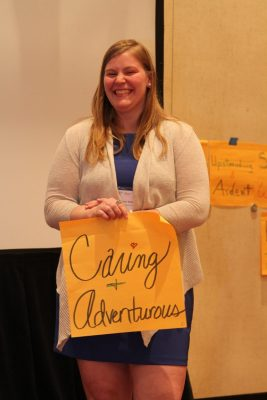 "Amber Bradley holds up sign with the words ""caring and adventurous"" on it."