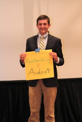 "Brad Douglas holds up sign with the words ""upstanding and ardent"" on it."