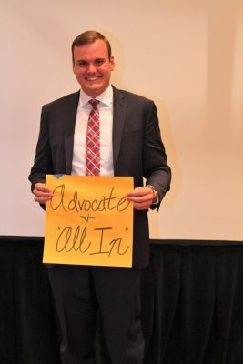 "Chandler Vaughn holds up sign with the words ""advocate and 'all in'"" on it."