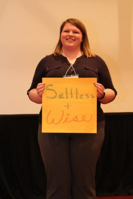 "Elizabeth Pittman holds up sign with the words ""selfless and wise"" on it."