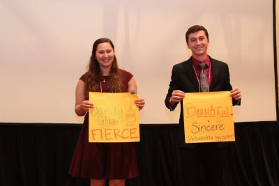 "Kelly  Casper and Will Jones stand holding their descriptive adjective signs with the words ""'family glue' and fierce"" and ""beautiful and sincere."""