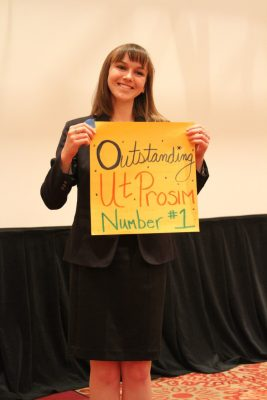 "Megan Mclaughlin holds up sign with the words ""outstanding, 'ut prosim,' and 'number 1'"" on it."