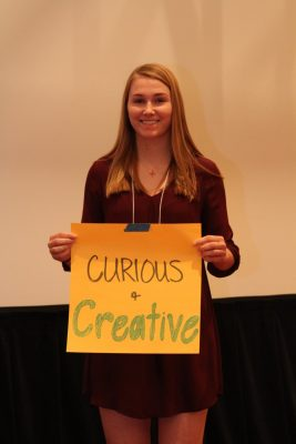 "Shelby Iager holds up sign with the words ""curious and creative"" on it."