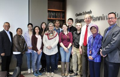 Indonesian visitors stand with AAEC trade center officials and graduate students.