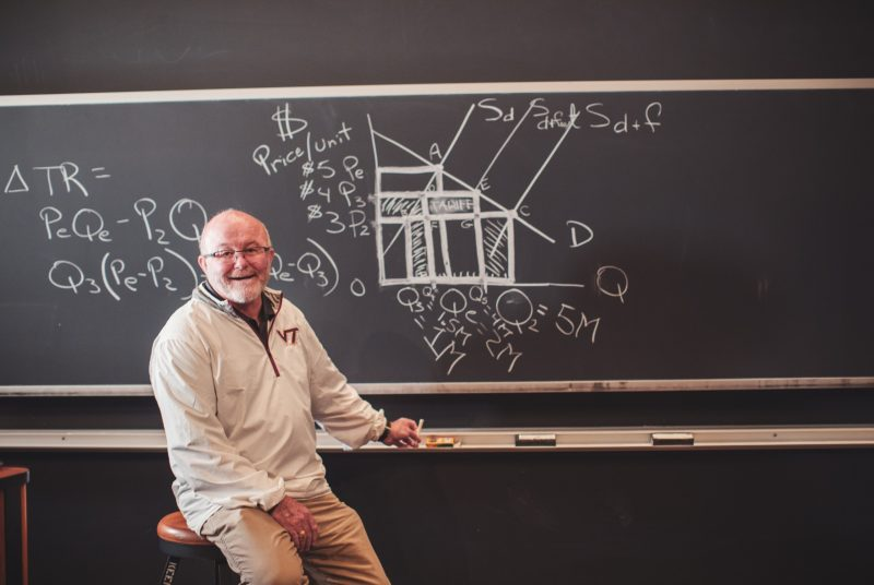Professor Mike Ellerbrock sits in front of chalkboard after drawing economic diagram.